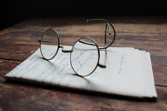 silver framed eyeglasses on white printer paper